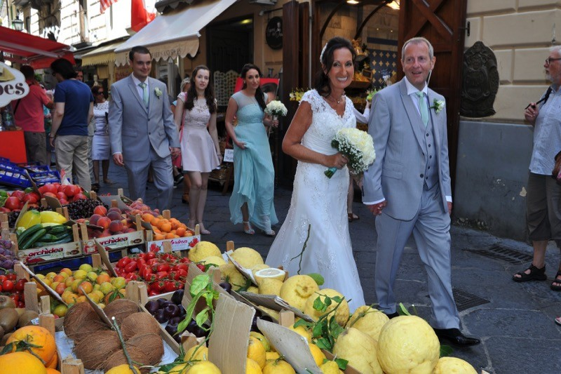 bride and groom walk in front of fruit stand in Sorrento, Italy | Planner: Venice Events | via https://emmalinebride.com/real-weddings/italian-weddings-destination/