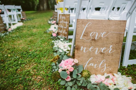 Love never fails ceremony aisle signs by Paper and Pine Co | via Wood Themed Wedding Ideas: https://emmalinebride.com/themes/wood-themed-wedding-ideas/