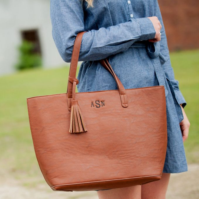 Leather tote bag with monogram and tassel detail by Carolina Dandy via 21 Festive Tassel Wedding Decorations & Accessories | http://emmalinebride.com/themes/tassel-wedding-decorations/ width=