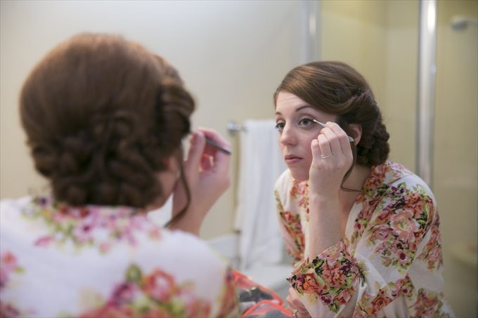 bride getting ready in mirror in this Crystal Coast Wedding | North Carolina wedding photographed by Ellen LeRoy Photography - https://emmalinebride.com/real-weddings/breathtaking-crystal-coast-wedding-mara-will-married/