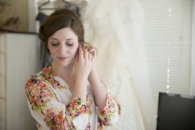 bride putting on earrings in this Crystal Coast Wedding | North Carolina wedding photographed by Ellen LeRoy Photography - https://emmalinebride.com/real-weddings/breathtaking-crystal-coast-wedding-mara-will-married/