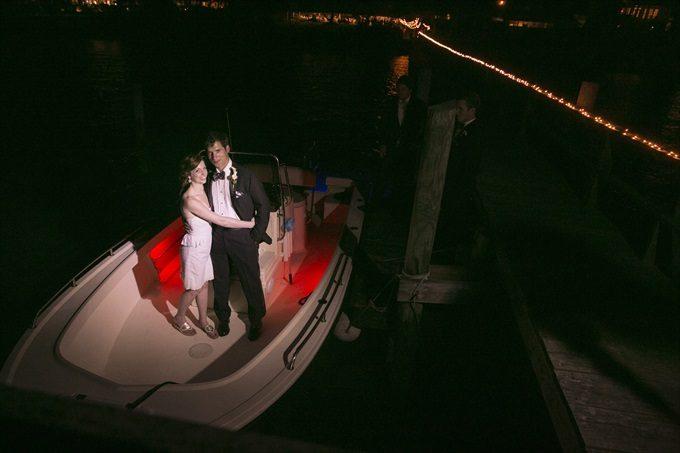bride and groom leave wedding on boat at night in this Crystal Coast Wedding | North Carolina wedding photographed by Ellen LeRoy Photography - http://emmalinebride.com/real-weddings/breathtaking-crystal-coast-wedding-mara-will-married/