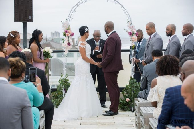 the bride and groom standing in front of the flower arch at the ceremony