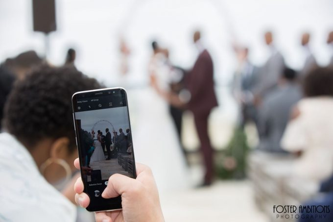photo of a guest taking a photo on their phone at the ceremony