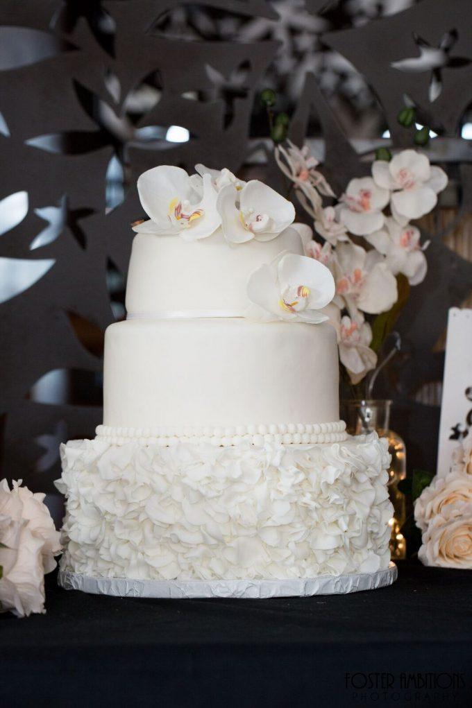 the wedding cake was topped with orchids