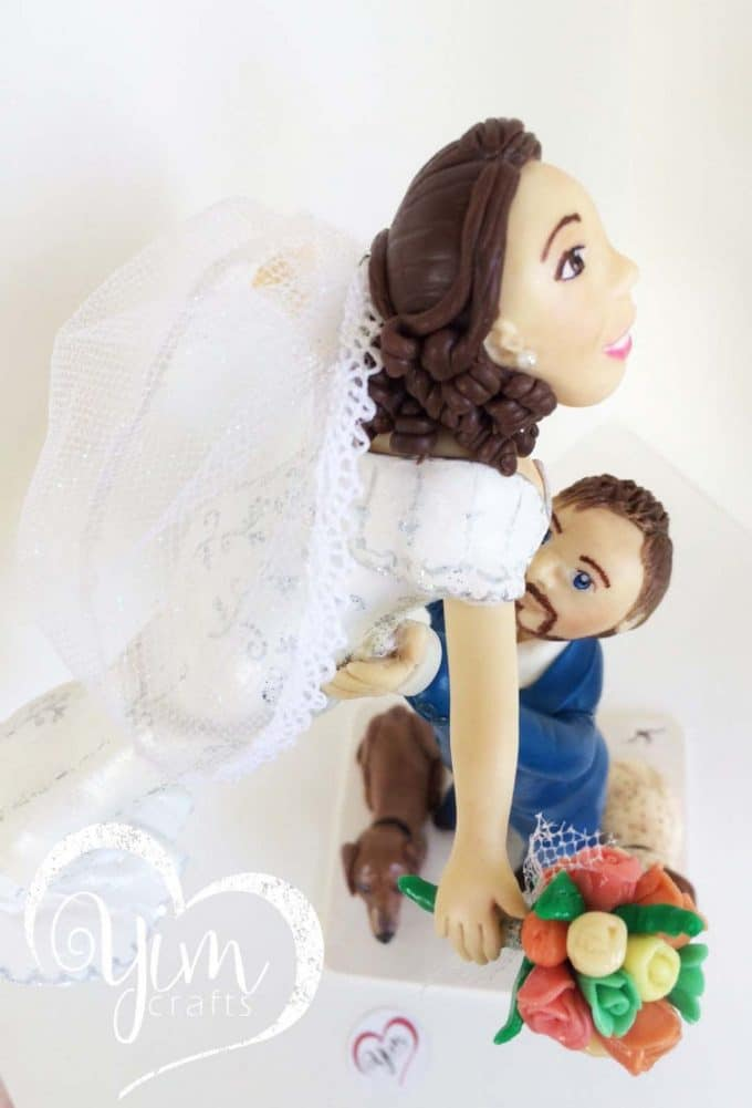 bride lifted by groom cake topper