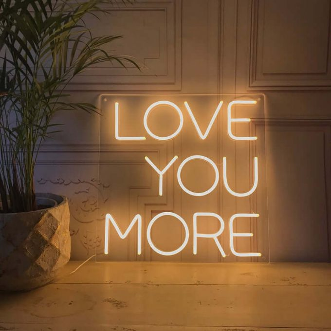 neon sign that says love you more