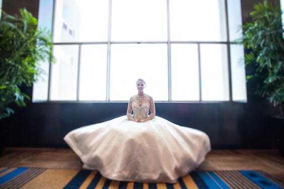 bride sitting in wedding dress at Lowes Hotel - Crystal Tea Room Wedding - photo: Daniel Fugaciu Photography | via https://emmalinebride.com