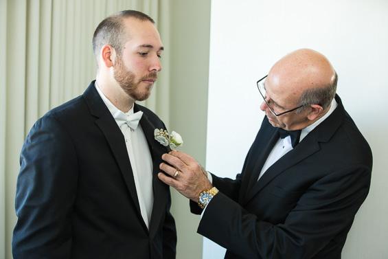 groom's father pins boutineer - Crystal Tea Room Wedding - photo: Daniel Fugaciu Photography | via https://emmalinebride.com