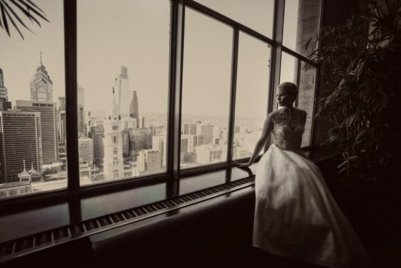 bride looking out Lowes Hotel window at Philadelphia - Crystal Tea Room Wedding - photo: Daniel Fugaciu Photography | via https://emmalinebride.com