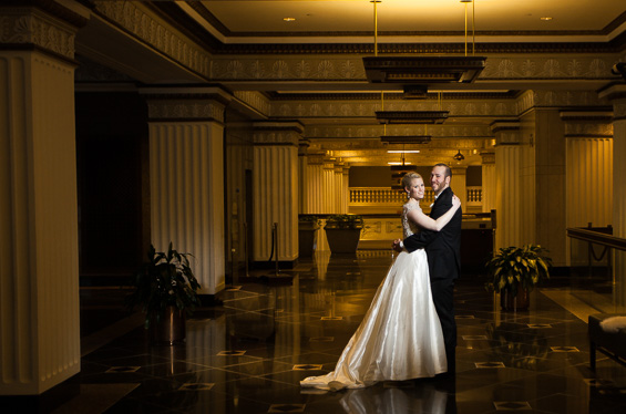 bride and groom pose in Lowes Hotel Lobby - Crystal Tea Room Wedding - photo: Daniel Fugaciu Photography | via https://emmalinebride.com