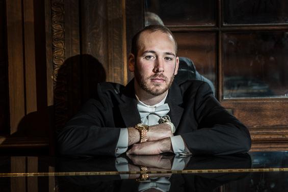 groom poses sitting at piano - photo: Daniel Fugaciu Photography | via https://emmalinebride.com