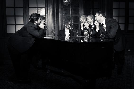 fun photo of groom playing piano surrounded by groomsmen - photo: Daniel Fugaciu Photography | via https://emmalinebride.com