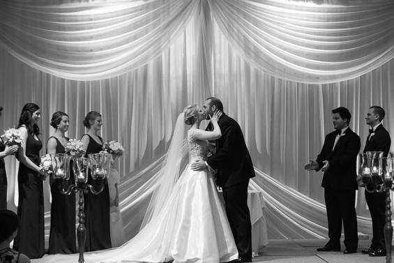 bride kisses groom at alter - photo: Daniel Fugaciu Photography | via https://emmalinebride.com