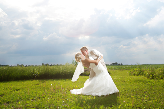 KimAnne Photography - iowa backyard wedding - bride-groom-kiss-outdoors-under-sun