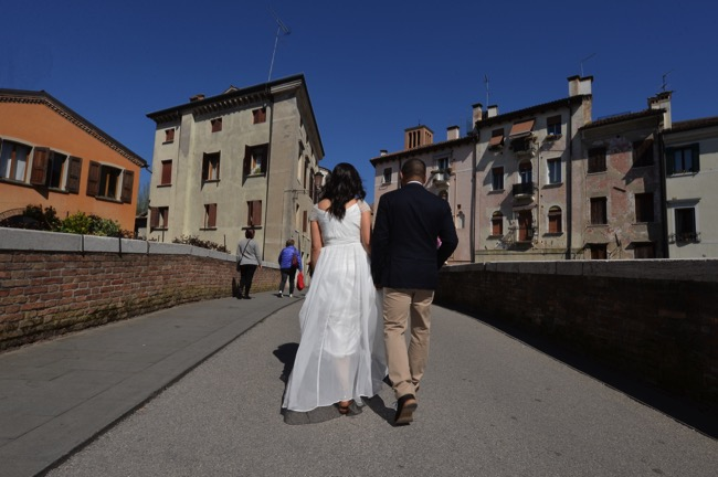 bride and groom walk across bridge at their spring wedding in Italy | Planner: Venice Events | via https://emmalinebride.com/real-weddings/spring-wedding-in-italy-andre-shona/