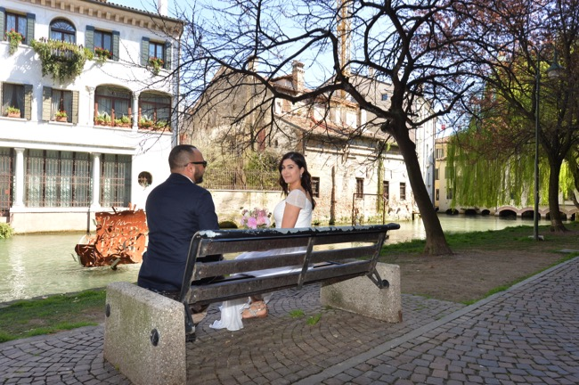 bride and groom sit on bench in Treviso | Planner: Venice Events | via https://emmalinebride.com/real-weddings/spring-wedding-in-italy-andre-shona/