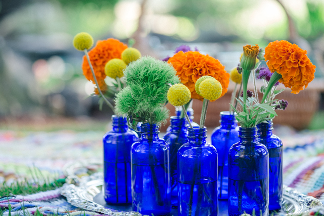 floral arrangements in blue bottles| Photo: White Ivory Photography | via https://emmalinebride.com/real-weddings/hipster-engagement-session-what-does-one-look-like/