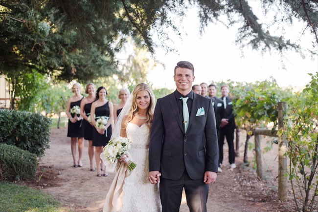 bride and groom in front of wedding party, bridesmaids wearing one-shoulder black dresses
