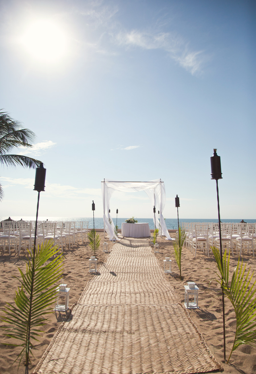 aisle with mat lined with tiki torches and white lanterns for beach ceremony | photo: victoria anne | via decorate for beach wedding ideas from emmalinebride.com