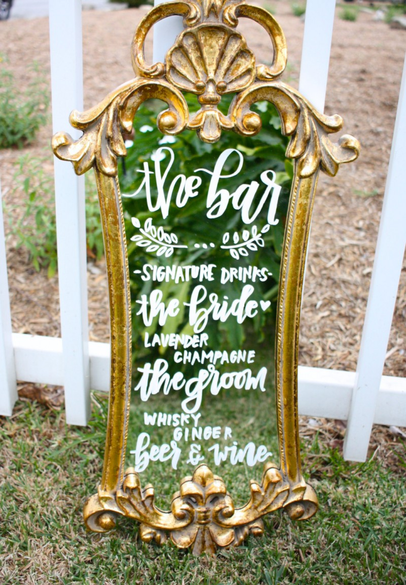 This decorative bar mirror is one of our favorite wedding mirror signs!  It's ideal for displaying a signature cocktail. | https://emmalinebride.com/decor/wedding-mirror-signs/