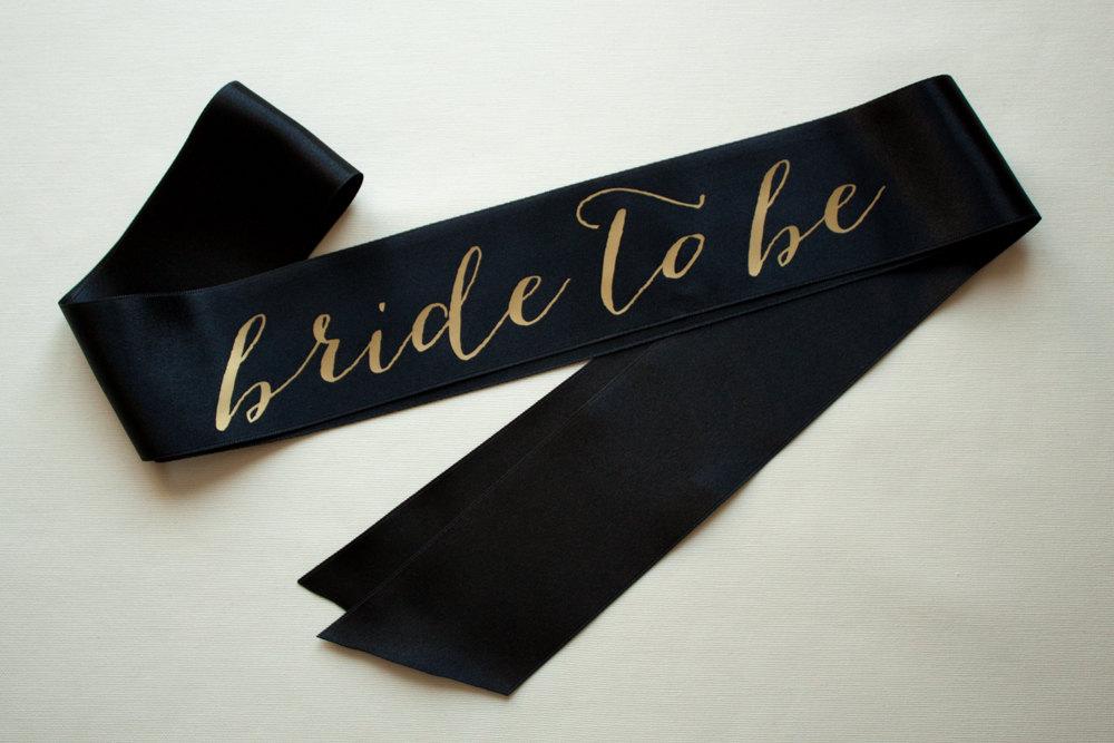 black bride to be sash with gold | stylish bachelorette sash ideas | via https://emmalinebride.com/bride/bachelorette-sash-ideas/