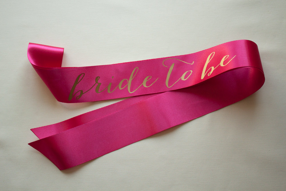 bride to be gold on hot pink sash | stylish bachelorette sash ideas | via https://emmalinebride.com/bride/bachelorette-sash-ideas/