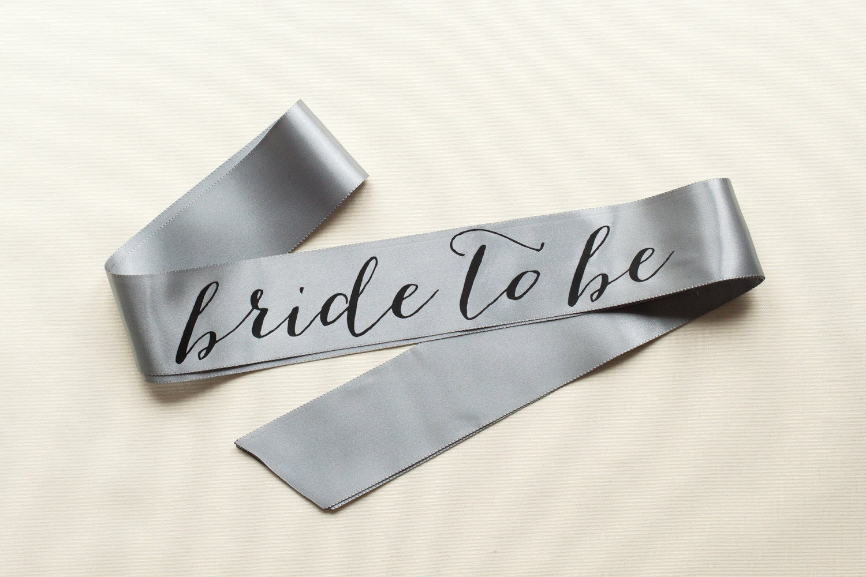 bride to be sash silver with black text | stylish bachelorette sash ideas | via https://emmalinebride.com/bride/bachelorette-sash-ideas/
