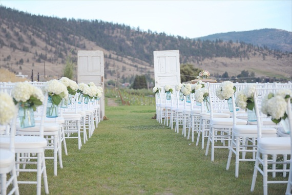decorate the ceremony aisle with hanging blue mason jar vases filled with flowers hanging mason jar vases