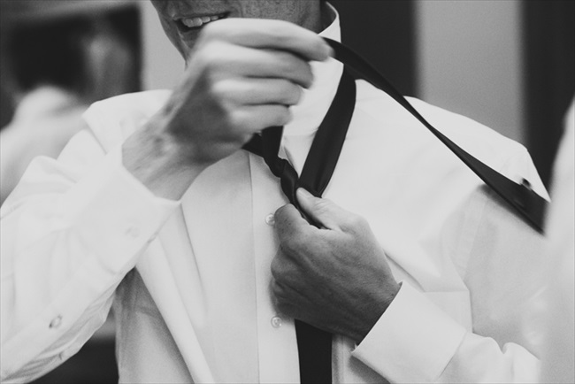 The groom putting on his tie | Photo: Searching for the Light Photography LLC | via https://emmalinebride.com/real-weddings/colorado-chic-wedding-kendall-brian/
