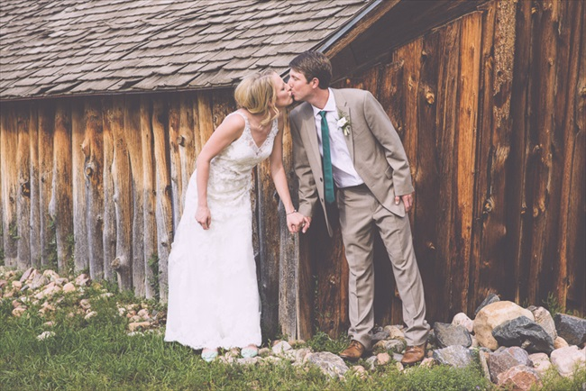 The bride and groom kiss in front of the barn | Photo: Searching for the Light Photography LLC | via https://emmalinebride.com/real-weddings/colorado-chic-wedding-kendall-brian/