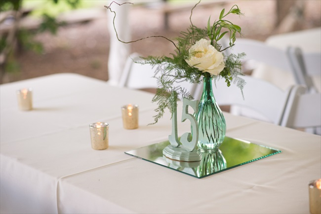 Easy DIY centerpiece idea:  a table number atop a mirror, white linens, a vase of flowers, and chic votive candles | Photo: Searching for the Light Photography LLC | via https://emmalinebride.com/real-weddings/colorado-chic-wedding-kendall-brian/