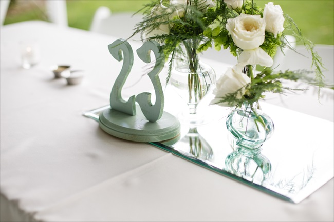 Table number and mirror with vase of flowers for centerpiece | Photo: Searching for the Light Photography LLC | via https://emmalinebride.com/real-weddings/colorado-chic-wedding-kendall-brian/