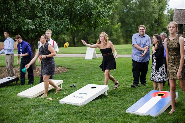 Guests played cornhole as entertainment before dinner | Photo: Searching for the Light Photography LLC | via https://emmalinebride.com/real-weddings/colorado-chic-wedding-kendall-brian/
