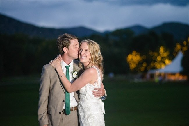 The groom kisses his bride | Photo: Searching for the Light Photography LLC | via https://emmalinebride.com/real-weddings/colorado-chic-wedding-kendall-brian/