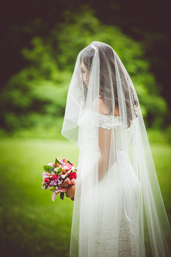 bride wearing long length wedding veil covering her face