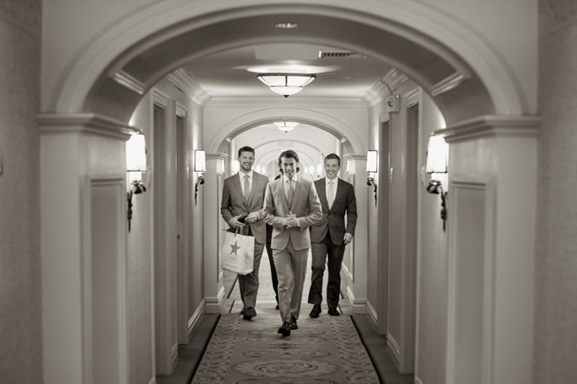 groom with groomsmen walking dawn hallway at Connecticut waterfront wedding - photo: Melani Lust Photography | via https://emmalinebride.com