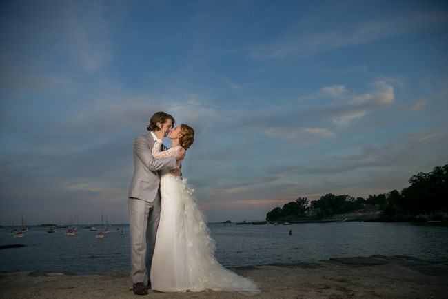 bride and groom kiss in Greenwich Harbor at Connecticut wedding - photo: Melani Lust Photography | via https://emmalinebride.com