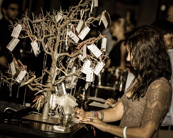 guest filling out wish tag wish tree - Wedding Wish Tree