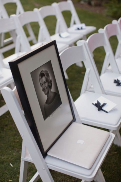 framed photo on chair at ceremony via How to Honor Loved Ones Who Have Passed at Wedding