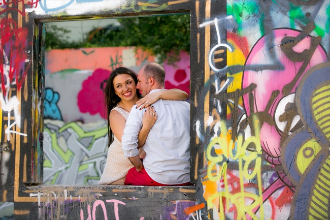 couple takes photo by graffiti at their Fun Austin Engagement Session | Photographer: Adrianne Riley Photography | via https://emmalinebride.com/real-weddings/fun-austin-engagement-session-priscella-jerry/
