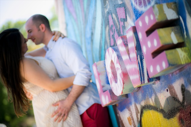 couple embraces by love sign at their Fun Austin Engagement Session | Photographer: Adrianne Riley Photography | via https://emmalinebride.com/real-weddings/fun-austin-engagement-session-priscella-jerry/