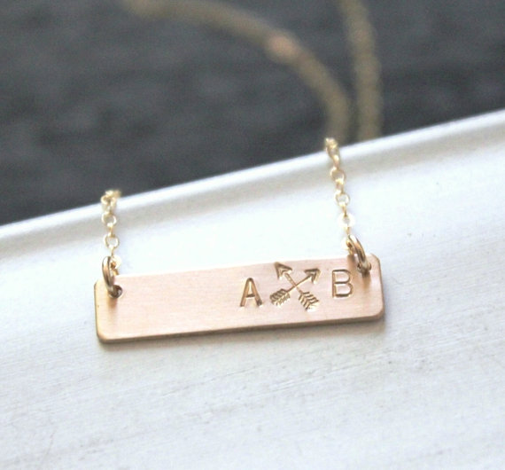 layering gold bar necklace with arrows and initials