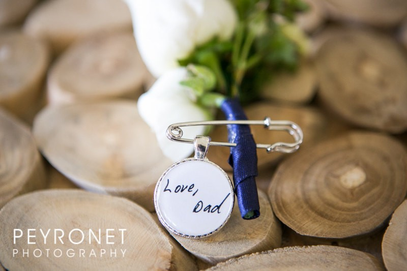 This boutonniere pin features a charm that is handwritten on one side and features a photo on the other. It is used as a way to remember a loved one who has passed at your wedding. | Handmade Wedding Charms via http://emmalinebride.com/decor/handmade-wedding-charms/