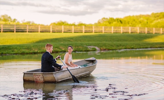 rowboat wedding photo of groom rowing bride in small lake