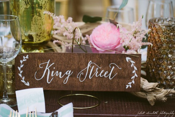 Use table names at your wedding instead of table numbers. Cute and creative idea! Sign by Paper and Pine Co. | Photo: Juliet Elizabeth Photography | table names weddings - https://emmalinebride.com/reception/table-names-weddings/