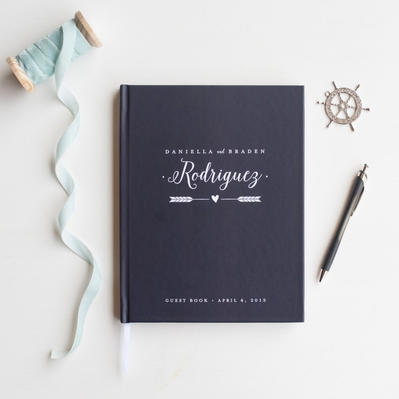 wedding guest book with arrow and personalized name in navy by starboard press