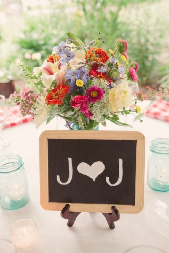 Decorate your centerpieces with a personal touch, like your wedding initials on a small chalkboard attached to a tabletop easel.