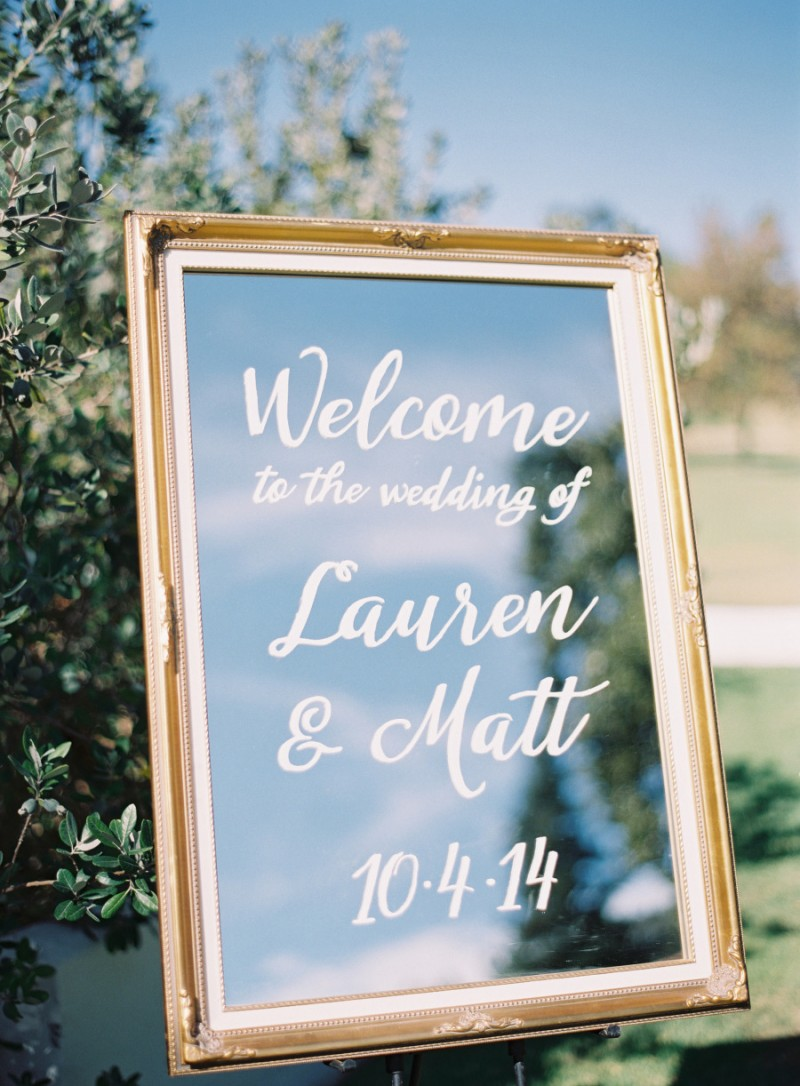 Use a mirror and paint to welcome guests to your wedding.  Photo: Rylee Hitchner | https://emmalinebride.com/decor/wedding-mirror-signs/